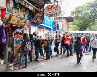 Queue of people in line for Hong Kong Style Egg Waffle street food, Hong Kong - Stock Photo