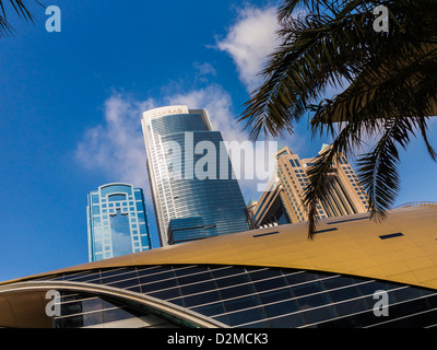 Conrad Hotel, Dubai (centre) with Fairmont Hotel (R) and curved roof of the World Trade Centre metro station in - Stock Photo