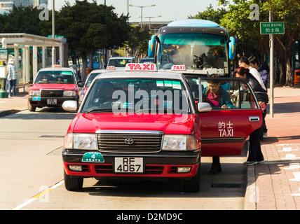 Hong Kong Taxi - people getting into taxis at a taxi rank, Hong Kong, China - Stock Photo
