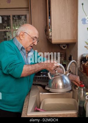 elderly man filling a kettle at kitchen sink - Stock Photo