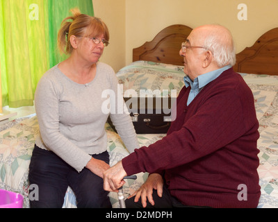 elderly man sat on bed in discussion with daughter - Stock Photo