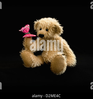 Cute hand made honey coloured teddy bear with black nose and a pink artificial butterfly on paw, taken on a black - Stock Photo