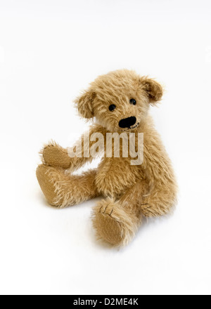 Cute hand made honey coloured teddy bear with a black stiched nose and sparse fur on a white background. - Stock Photo