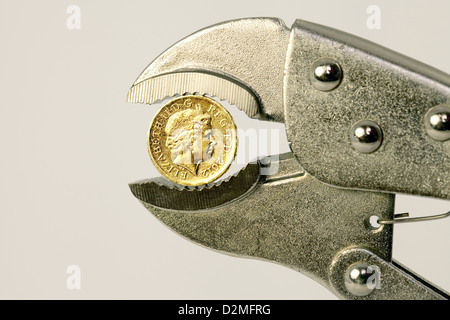 A british one pound coin in a wrench to illustrate the concept of the pound being under pressure, UK - Stock Photo