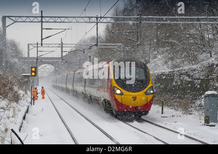 In snow a Virgin Trains Class 390 Pendolino heads towards Birmingham New Street with a service from London Euston - Stock Photo