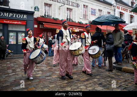 Young men march with drums in traditional costumes during a performance in the square on top of Montmartre, in Paris, - Stock Photo