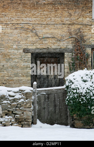 Cotswold stone thatched cottage with wooden front door, garden wall and wooden gate. Snow is falling and lays on - Stock Photo