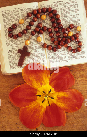 Bible or prayer book open at The Psalms with beaded crucifix pendant and open red and yellow tulip flower - Stock Photo