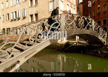 Exceptional metal bridge over canal with water reflections, and pedestrian, Venice, Veneto, Italy - Stock Photo