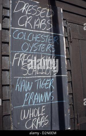 Blackboard outside black tarred fishermans hut advertising shellfish seafood for sale - Stock Photo