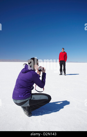 Couple taking photos on Salar de Uyuni (Salt Flats of Uyuni), Potosi Department, Bolivia, South America - Stock Photo