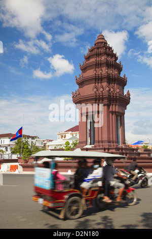 Tuk tuk passing Independence Monument, Phnom Penh, Cambodia, Indochina, Southeast Asia, Asia - Stock Photo