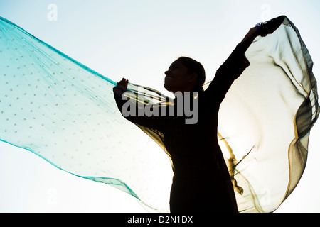 Indian girl with veils turning in the wind towards the sun. Silhouette. India - Stock Photo