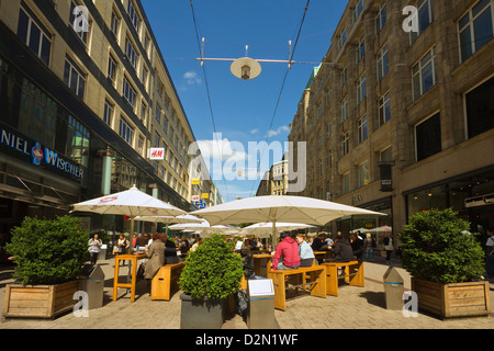 People sitting al fresco under parasols outside restaurant on pedestrianised shopping street, Spitalerstrasse, Hamburg, - Stock Photo