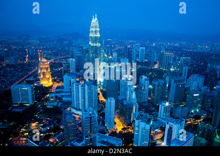 Night view over the financial district with Petronas Towers and more skyscrapers as seen from KL Tower, Kuala Lumpur, - Stock Photo