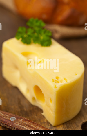 Piece of fresh organic edam cheese on wooden board with fresh bread on breakfast kitchen table - Stock Photo