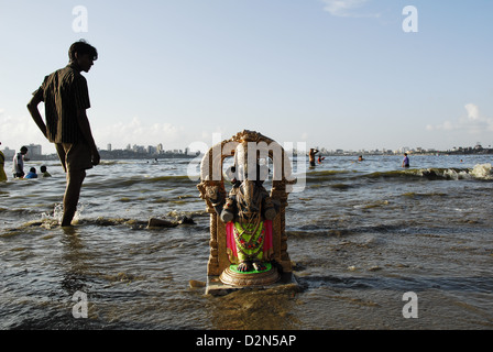 A Ganesha idol washes ashore in Mumbai, Maharashtra, India, Asia - Stock Photo