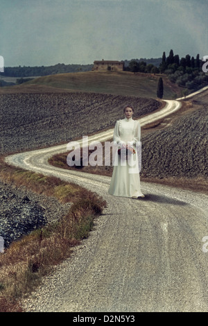a girl in a white dress is walking along a lane with a basket of flowers in a mediterranean landscape - Stock Photo