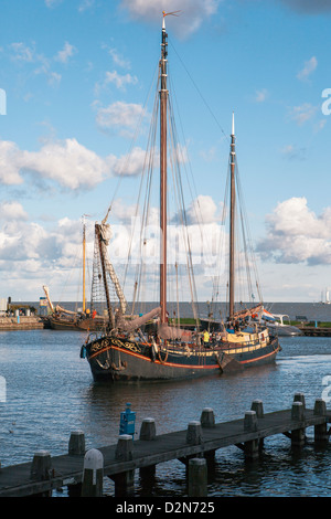 Traditional Dutch merchant ship sailing into Volendam harbour, North Holland Province, The Netherlands (Holland), - Stock Photo