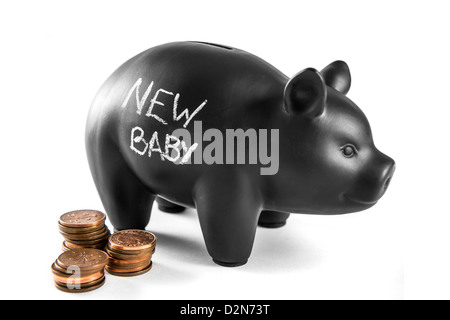 Black piggy bank on white background with 'new baby' written on it and three piles of 2 pence coins - Stock Photo
