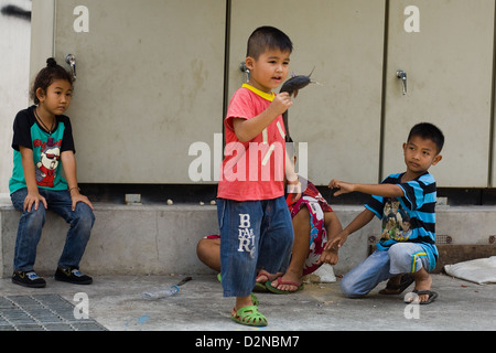 A boy holds of a fish that he has just caught from Chao Phraya river in Bangkok Thailand - Stock Photo