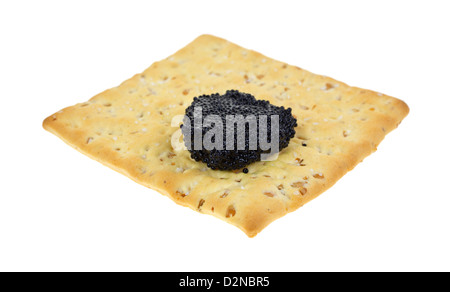 A stone ground wheat cracker with a small portion of black caviar on a white background. - Stock Photo