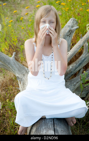 Young girl sitting on a log in summer surrounded by weeds and blowing her nose because of allergies - Stock Photo