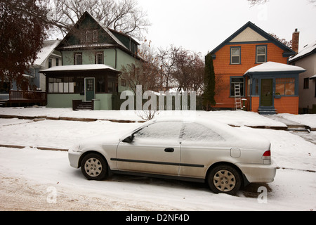 car covered in snow parked by the side of the street in front of residential homes caswell hill Saskatoon Saskatchewan - Stock Photo