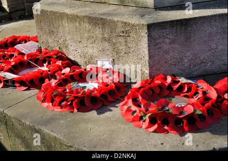 Poppy wreaths laid on war memorial - Stock Photo