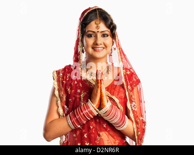 Bride in traditional wedding dress and making greeting gesture - Stock Photo