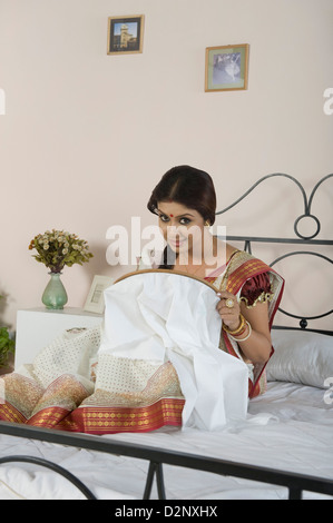 Woman doing embroidery work in the bedroom - Stock Photo