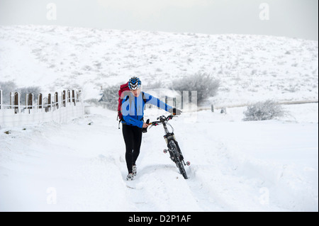 A brave cyclist pushes his bike through snow on the A39 which is blocked due to snow causing havoc on Devon Somerset - Stock Photo