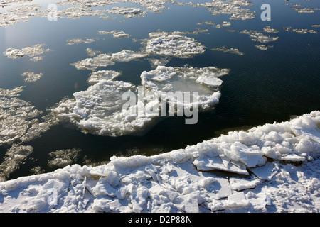 large chunks of floating ice on the south saskatchewan river in winter flowing through downtown Saskatoon Saskatchewan - Stock Photo
