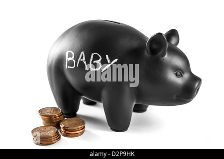 Black piggy bank on white background with 'baby' written on it and three piles of 2 pence coins - Stock Photo