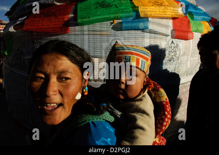 tibetan mother and child by prayer flags in lhasa, tibet - Stock Photo