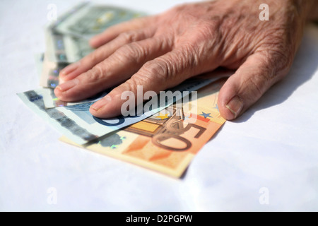 Berlin, Germany, the hands are a pensioner on banknotes - Stock Photo