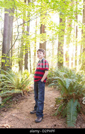 Caucasian boy standing on path in forest - Stock Photo