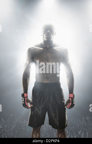 Light shining from behind African American MMA boxer - Stock Photo