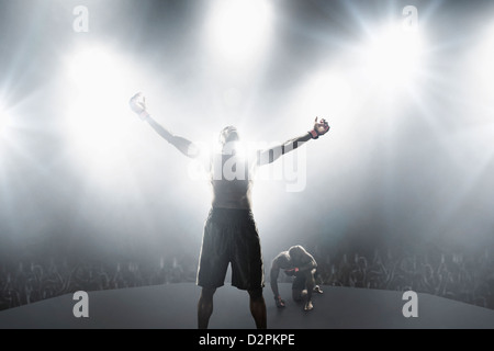 Light shining from behind winning African American MMA boxer - Stock Photo