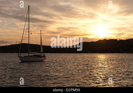 yacht on anchor in the bay with romantic sunset in background - Stock Photo