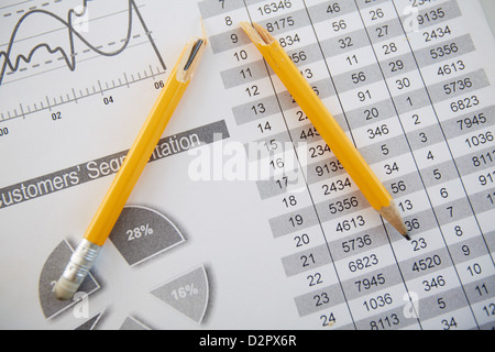 Close-up shot of a broken pencil lying over printed statistics - Stock Photo