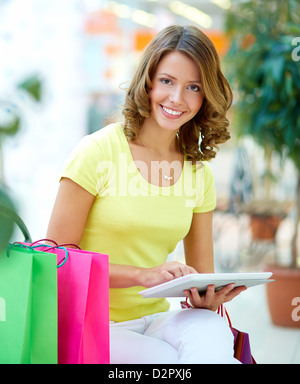 Vertical portrait of a young shopping woman using a touchpad - Stock Photo