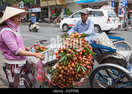 A cycle rickshaw driver stops to buy fruit from a lady outside Ben Thanh Market, Ho Chi Minh, Vietnam, Indochina - Stock Photo