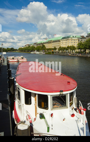 One of the tour boats that ply the Alster Lake, moored at the Jungfernstieg with the Ballindamm beyond, Hamburg, - Stock Photo