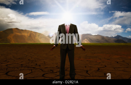 Businessman standing on a cracked landscape - Stock Photo