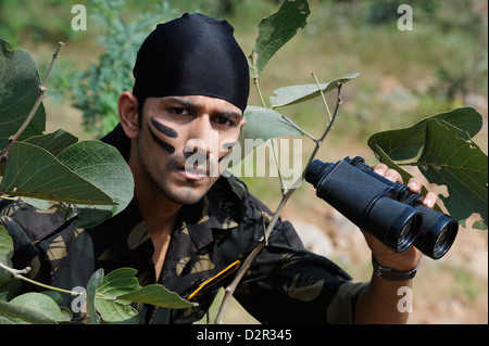 Soldier holding binoculars in a forest - Stock Photo