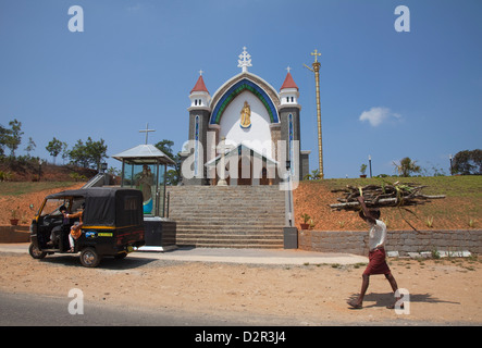 Man carrying firewood on his head walking past a church in rural Kerala, India, Asia - Stock Photo