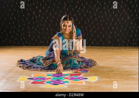 Woman talking on a mobile phone and making rangoli - Stock Photo