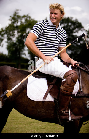 Portrait of polo player on pony holding reins - Stock Photo