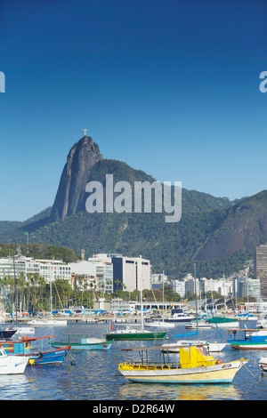 Boats moored in harbour with Christ the Redeemer statue in background, Urca, Rio de Janeiro, Brazil, South America - Stock Photo